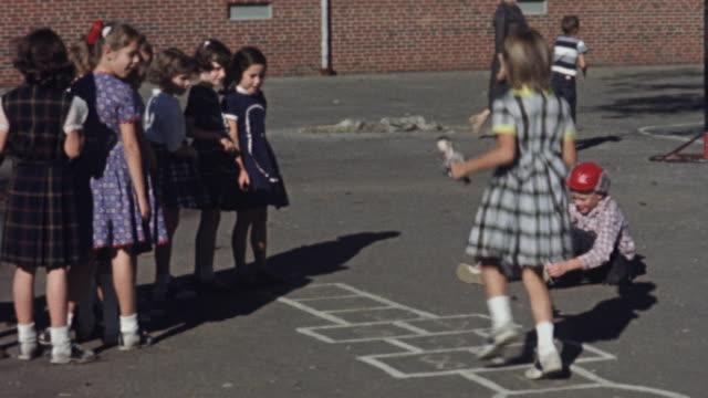 1956 WS Girls playing hopscotch / USA
