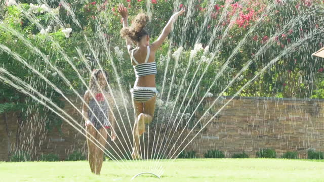 vídeos de stock, filmes e b-roll de 2 girls playing in a water sprinkler - aspersor