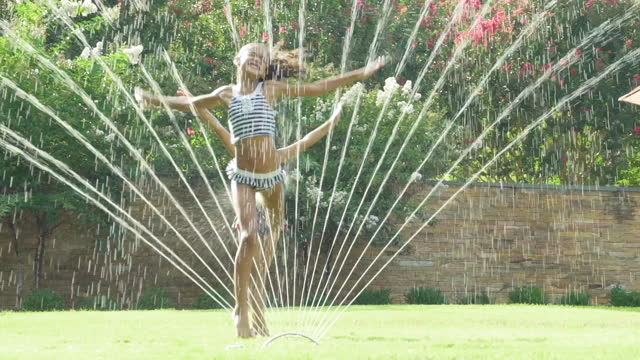 2 girls playing in a water sprinkler - lawn stock videos & royalty-free footage