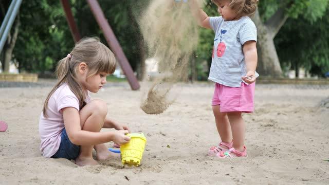 stockvideo's en b-roll-footage met girls playing in sand pit - hongarije