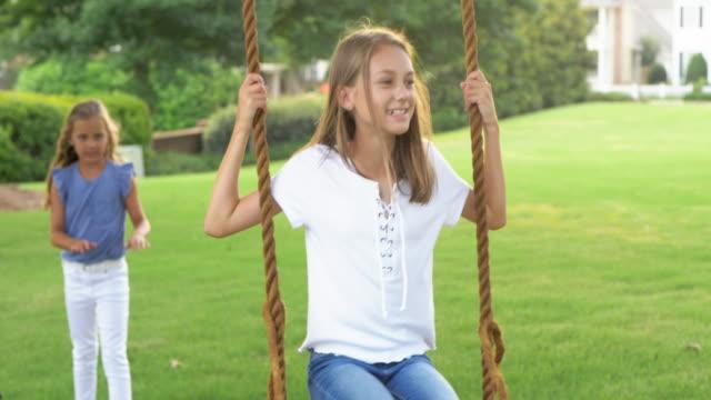 vidéos et rushes de jeunes filles jouant sur la balançoire dans le parc. - balançoire