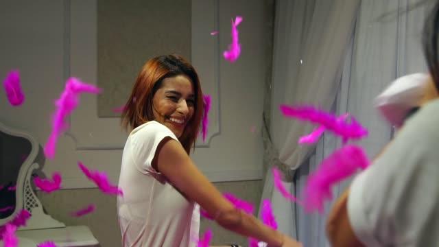 vídeos de stock, filmes e b-roll de garotas jogando travesseiro lutam em casa - saliente