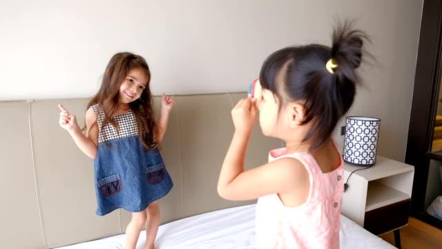stockvideo's en b-roll-footage met meisjesspelen neem een foto op het bed - acteren