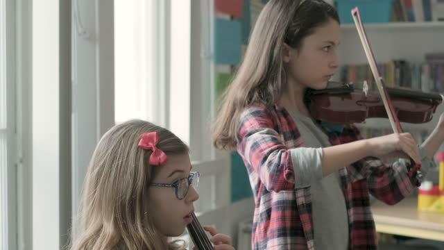 vidéos et rushes de girls playing violin and cello during lesson - violoncelle