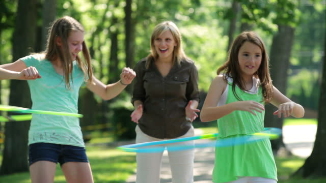 ms girls playing with hula hoop and mother watching / summit, new jersey, united states - famiglia con due figli video stock e b–roll