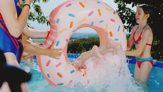 ms girls playing,umping through inflatable ring in swimming pool - inflatable stock videos & royalty-free footage