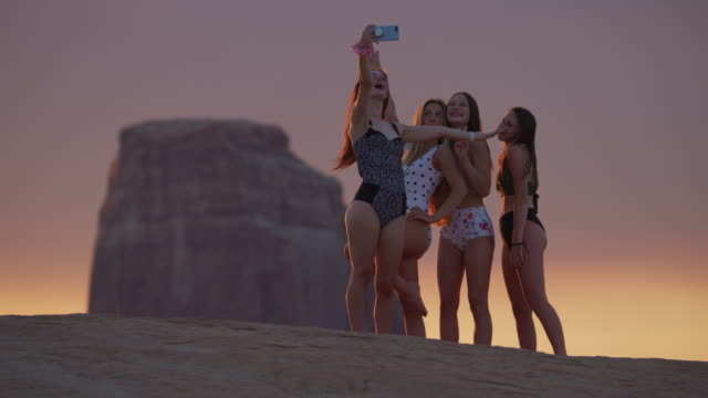 girls posing for cell phone selfies near rock formation at dusk / glen canyon national park, utah, united states - dreiviertelansicht stock-videos und b-roll-filmmaterial