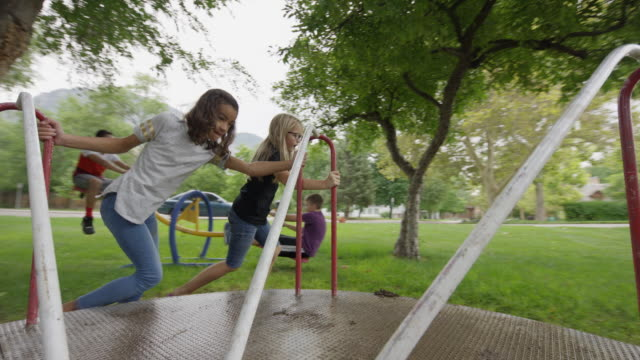girls pushing and riding neighborhood playground merry-go-round / provo, utah, united states - provo stock videos & royalty-free footage