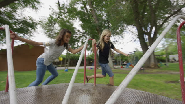 Girls pushing and riding neighborhood playground merry-go-round / Provo, Utah, United States