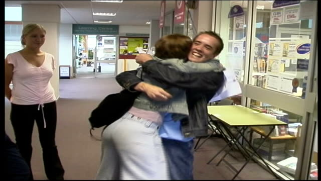 girls reacting happily to gcse results boy and girl embrace vox pops sot manchester: audenshaw school: secondary schoolboys receiving gcse results... - schoolboy stock videos & royalty-free footage