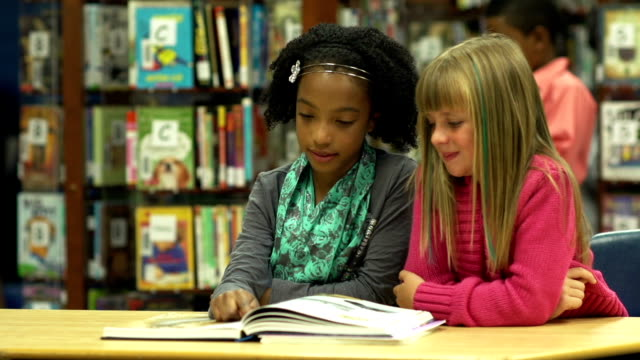 girls reading in the library - picture book stock videos and b-roll footage