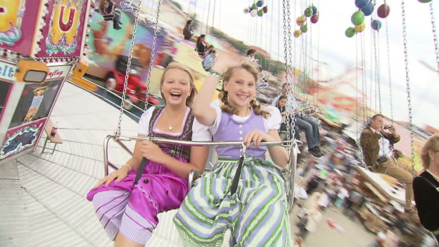 girls ride a carousel, in front
