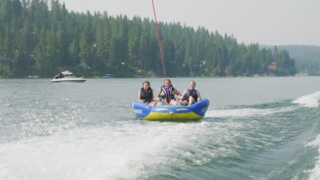 女の子スキー ボートの後ろにチューブに乗って - 水泳用浮き輪点の映像素材/bロール