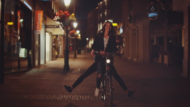 girls riding bike at night - piacere video stock e b–roll