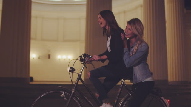 girls riding bike at night - vita cittadina video stock e b–roll