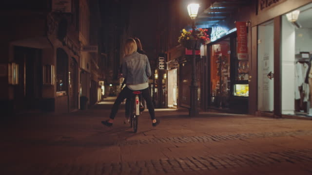 vídeos de stock e filmes b-roll de girls riding bike at night - vida urbana