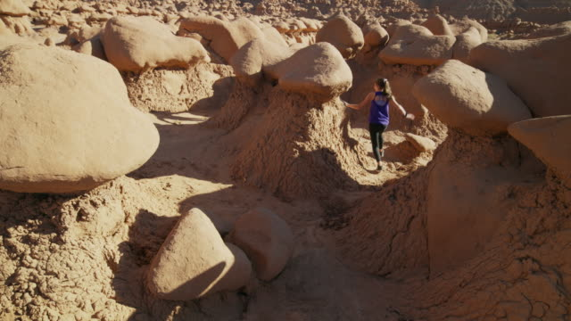 girls running and playing tag near rocks in desert / goblin valley, utah, united states - playing tag stock videos & royalty-free footage