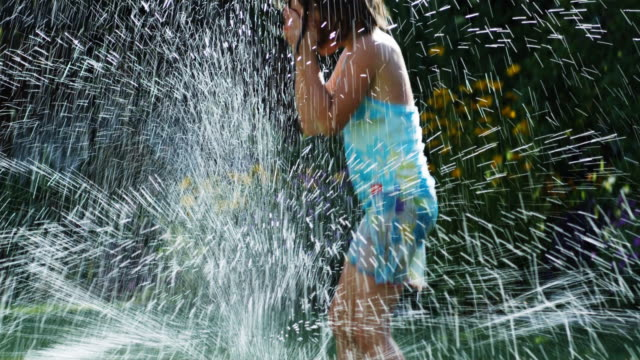 vídeos de stock, filmes e b-roll de girls running in a sprinkler - aspersor