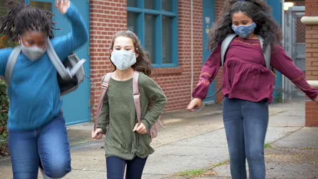 girls running outside elementary school with face masks - 8 9 years stock videos & royalty-free footage