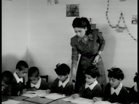 girls seated at low table female teacher instructing teaching iranian girls . iranian girl w/ teacher leaning bg. - 1951 stock videos & royalty-free footage