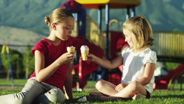 vídeos de stock, filmes e b-roll de ms girls (4-11) sharing ice cream, sitting on grass in playground / orem, utah, usa - dividir
