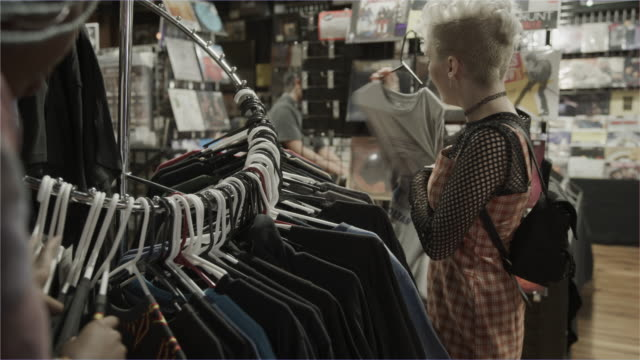 girls shopping for t-shirts in music store / provo, utah, united states - telecamera traballante video stock e b–roll