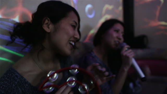 CU Girls sing and shake a tambourine in a karaoke club in Tokyo / Tokyo, Japan