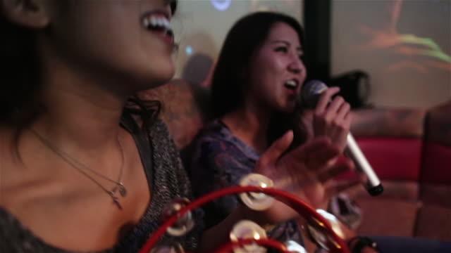CU Girls sing and shake a tambourine in a karaoke club in Tokyo / Tokyo, Japan