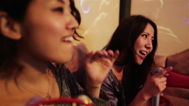 CU Girls sing and shake a tambourine quickly in a karaoke club in Tokyo / Tokyo, Japan