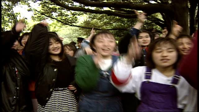 girls singing along to band in park in harajuku, japan - 1990年点の映像素材/bロール