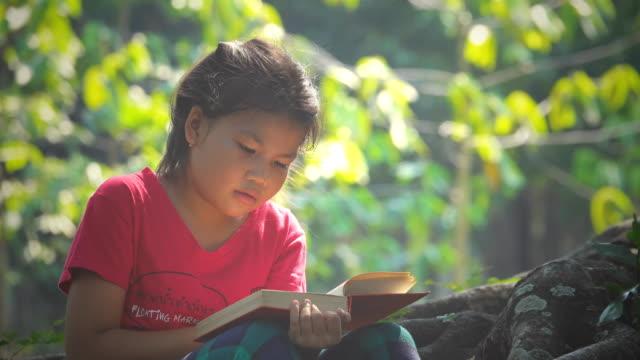 vidéos et rushes de les filles s'asseoit et lit un livre sous l'arbre sur une journée ensoleillée d'été - brightly lit