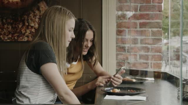 vídeos de stock e filmes b-roll de girls sitting at window in pizzeria checking social media on cell phone / provo, utah, united states - provo