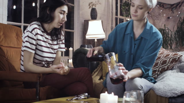 girls sitting on the sofa drinking wine catching up at home - 25 29 years stock videos and b-roll footage