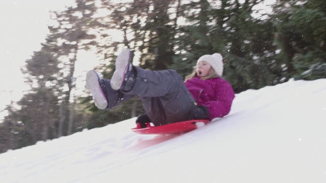 4k girls sledding on snowy slope, slow motion - ski holiday stock videos & royalty-free footage