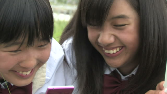 cu girls smiling, looking at mobile phone - japanese school uniform stock videos & royalty-free footage