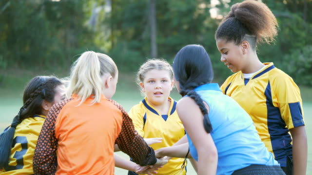 mädchen-fußball-team und trainer huddle und jubeln - multi ethnic group stock-videos und b-roll-filmmaterial