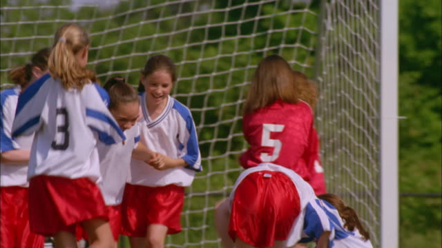 a girl's soccer team jumps up and down celebrating a win. - goal stock videos & royalty-free footage