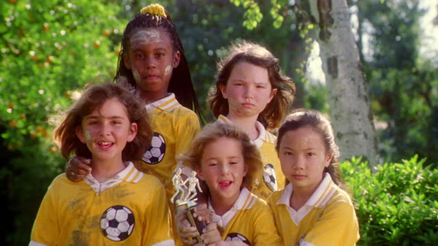 portrait girls soccer team with muddy faces + uniforms smiling + posing with trophy outdoors - mud stock videos & royalty-free footage