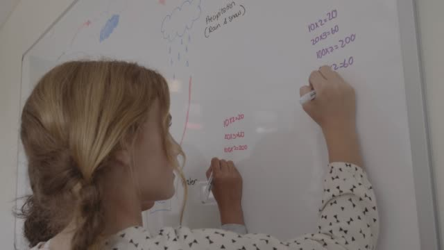 vídeos y material grabado en eventos de stock de girls solving multiplication on whiteboard - niña en edad escolar