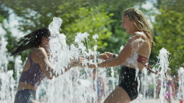Girls spinning and splashing in park fountain / Provo, Utah, United States