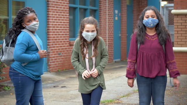 girls standing outside elementary school with face masks - 8 9 years stock videos & royalty-free footage