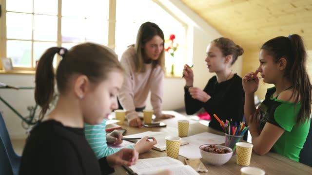 flickor som studerar tillsammans på privatlektioner med dam lärare - matte bildbanksvideor och videomaterial från bakom kulisserna