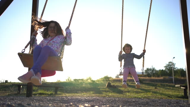 girls swinging on the playground at sunset - courage stock videos & royalty-free footage