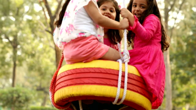 ms girls swinging on tyre swing in garden / delhi, india - tyre swing stock videos & royalty-free footage