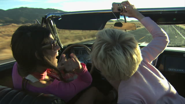 girls taking a photo and dancing while riding in a convertible - see other clips from this shoot 1138 stock videos and b-roll footage