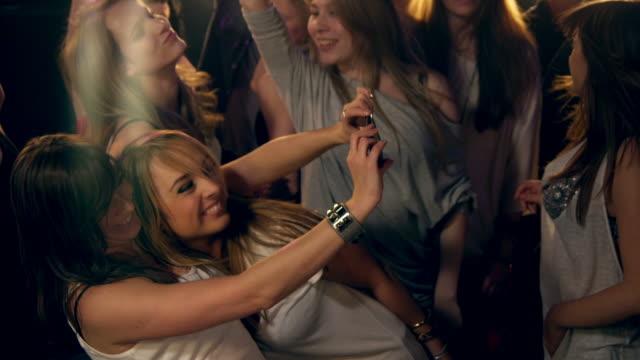 vídeos y material grabado en eventos de stock de chicas tomando fotos en la discoteca - photographing