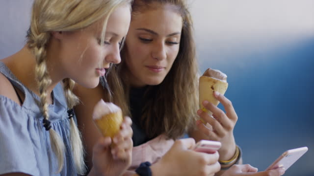 girls texting on cell phone and eating ice cream cones / provo, utah, united states - provo stock videos & royalty-free footage