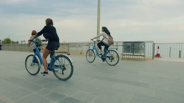 Girls together ride bicycles in the city