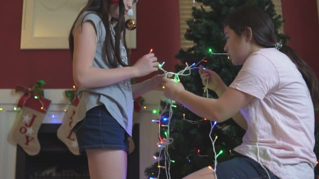 vídeos de stock e filmes b-roll de girls untangling christmas lights for the tree - emaranhado