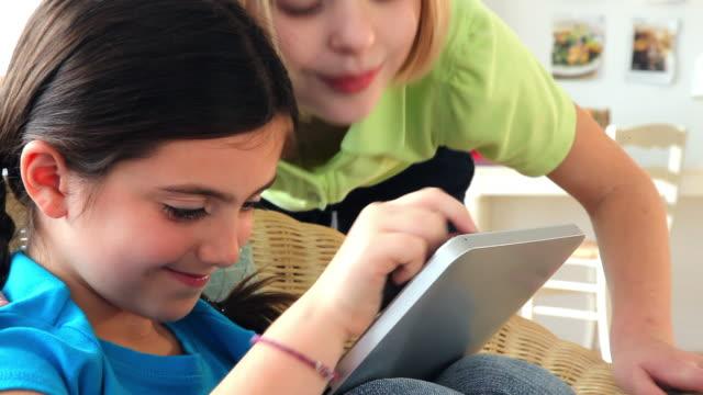 stockvideo's en b-roll-footage met girls using digital tablet in living room - bukken